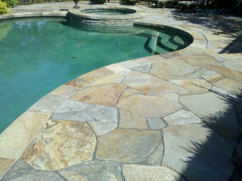 Stone masonry repair needed on this pool deck and patio. Masonry sealing and stone setting by Preferred Properties landscaping and masonry. (3/6)