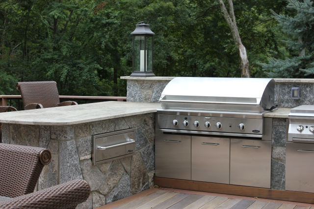This second story outdoor kitchen features outdoor fireplace with pizza oven off deck