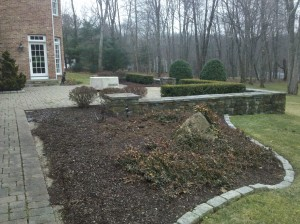 Outdoor living space before construction of marble patio with outdoor kitchen and firepit.